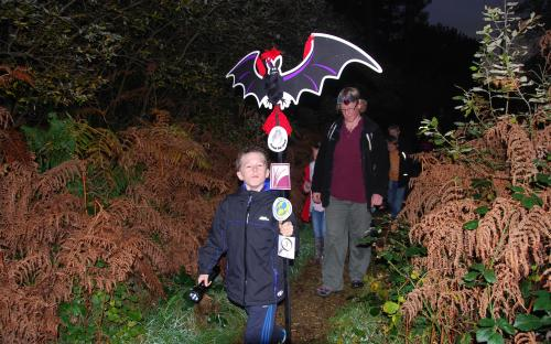 Child holds aloft glowing bat model