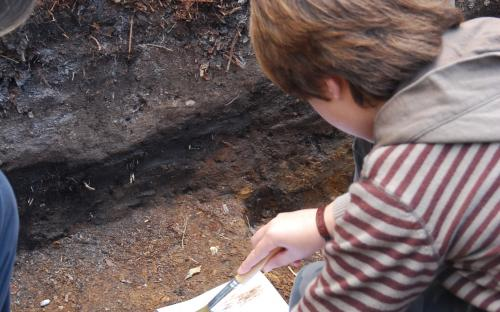 Child painting a soil profile in the trench`